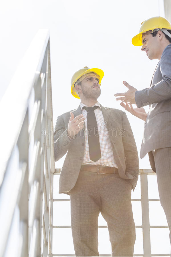 Low angle view of young male businessmen in hard hats having discussion on stairway against clear sky royalty free stock photography