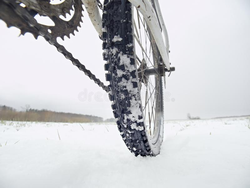 Low ankle photo of rear hweel of mtb in snowdrift. Picture taken within winter bike trip. In free landcape stock images