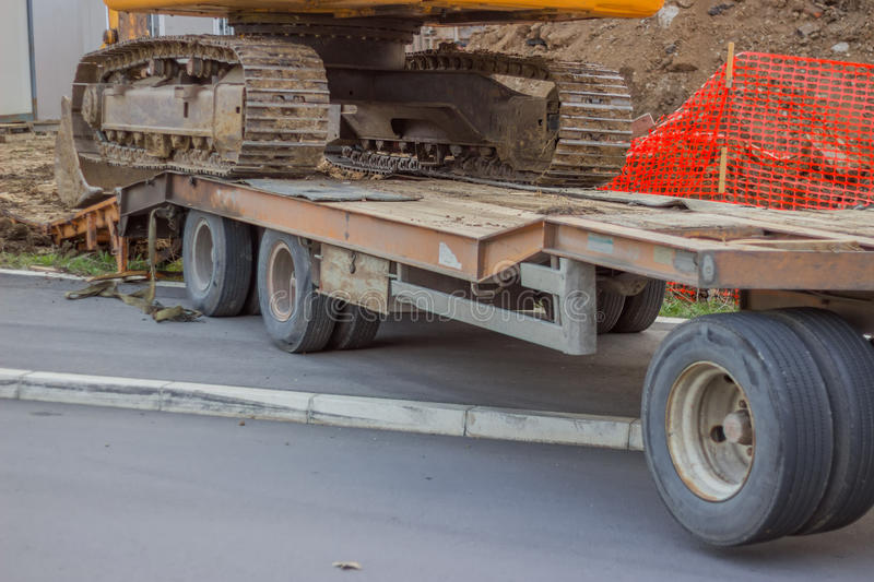 Low bed truck transporting excavator 2 royalty free stock image