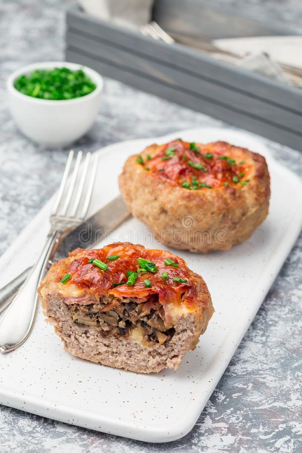 Low carb paleo meat cups, stuffed with champignons, bacon and cheese, garnished with green onion, on  white plate, vertical royalty free stock images
