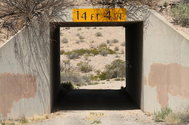Desert tunnel showing New Mexico scene. This is a low clearance tunnel or highway underpass showing a desert scene on the other side.  It is located on the back royalty free stock photo