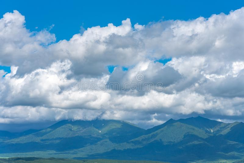 Low clouds over summer mountains green grass and blue sky stock photo