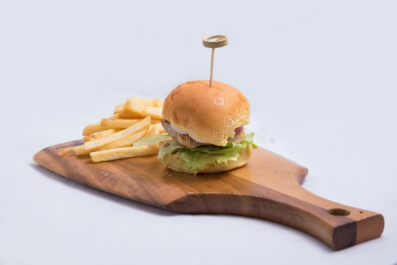 Lateral Hero Shot of a grilled chicken slider burger, fries on a wooden platter board, on a minimal white background with a stock photo