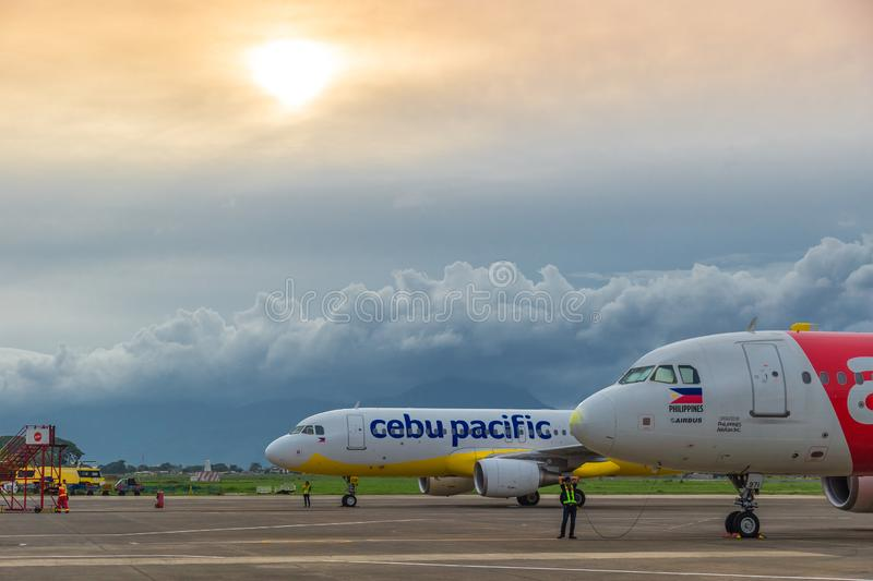 Low cost airlines Cebu Pacific and Air Asia aircraft at colorful sunset at Puerta Princesa Airport in Palawan island royalty free stock photo