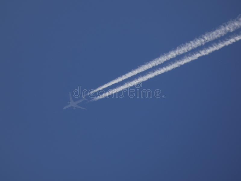 Plane furrowing the blue sky and leaving a white wake royalty free stock image