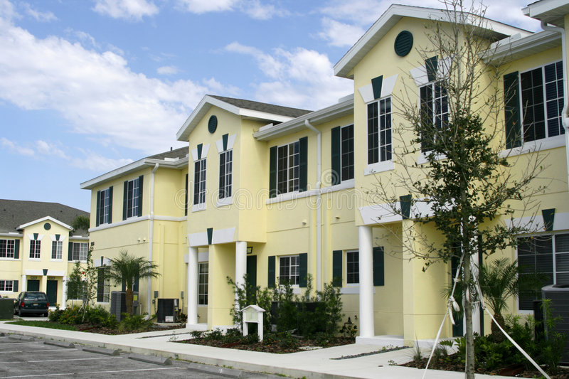 Low-cost housing condos. New low-cost housing condos in yellow with dark green trim and hurricane shutters and white columns,sidewalks and new landscaping royalty free stock images