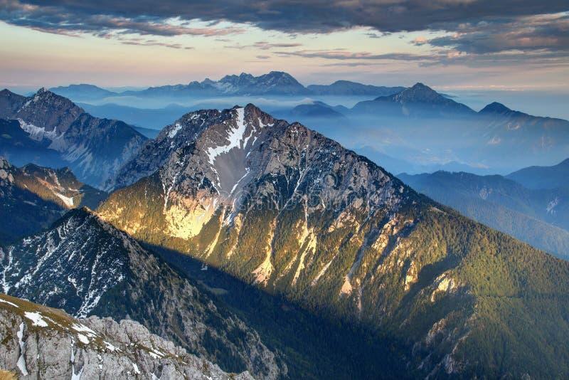 Low evening sunlight on ridges in hazy Karavanke / Kamnik Alps royalty free stock image