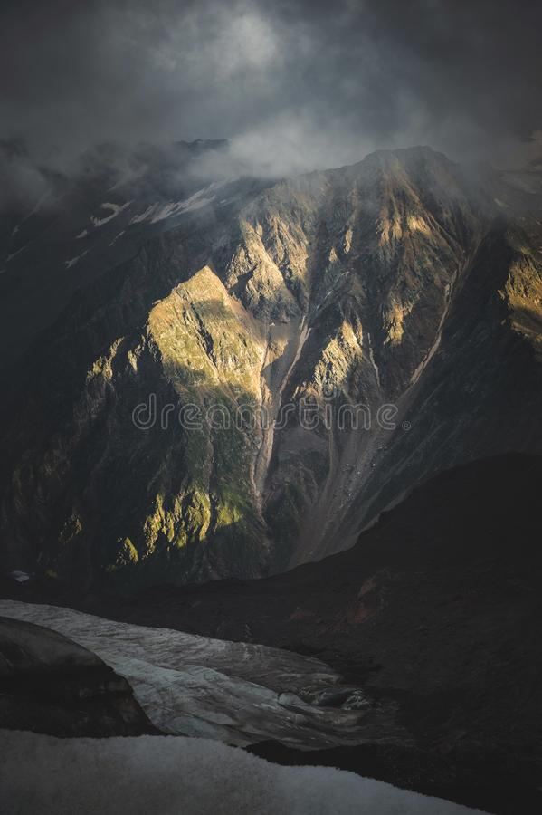 Low evening sunlight at sunset illuminates the sharp rocky ridges of the high stone walls of the Caucasus Mountains in stock images