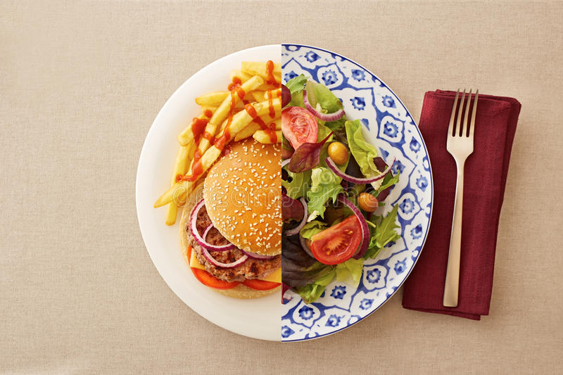 Low fat salad against greasy burger. Low fat healthy salad against unhealthy greasy burger royalty free stock image