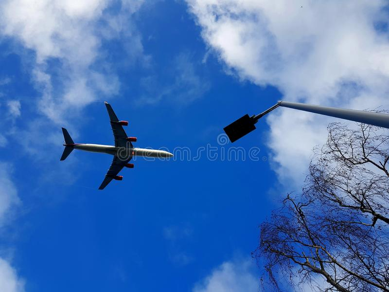 Low flying aircraft over London. Giving of fumes with trees and streetlights stock photos