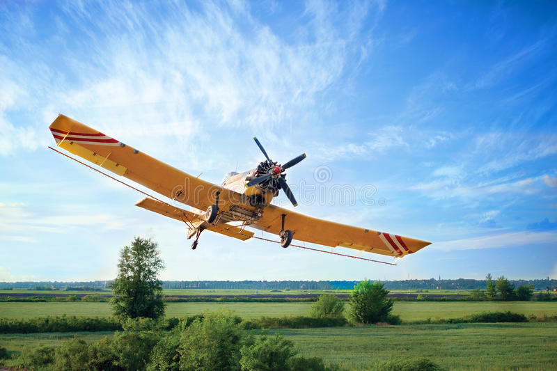 Low Flying Crop Duster against a blue sky stock photography