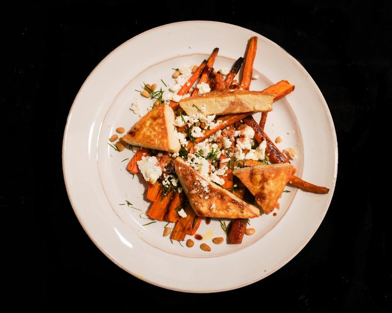A low FODMAP dinner of roasted carrots, goat cheese, tofu, pine nuts and dill  on a white plate isolated on a black background royalty free stock images