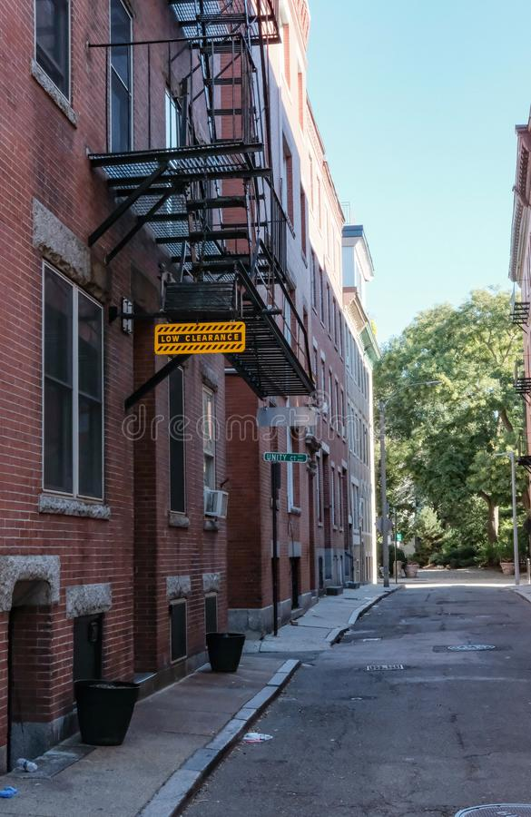 Low height clearance sign and fire escape seen in an American side street. royalty free stock photography