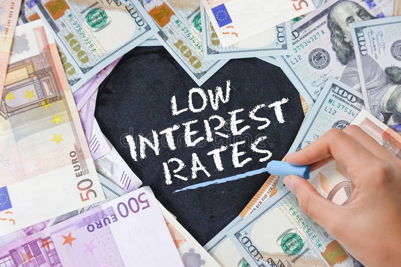 Low interest rate at mortgage loans, credit card or other types of loans, text in heart shape from cash banknotes in various curre stock image