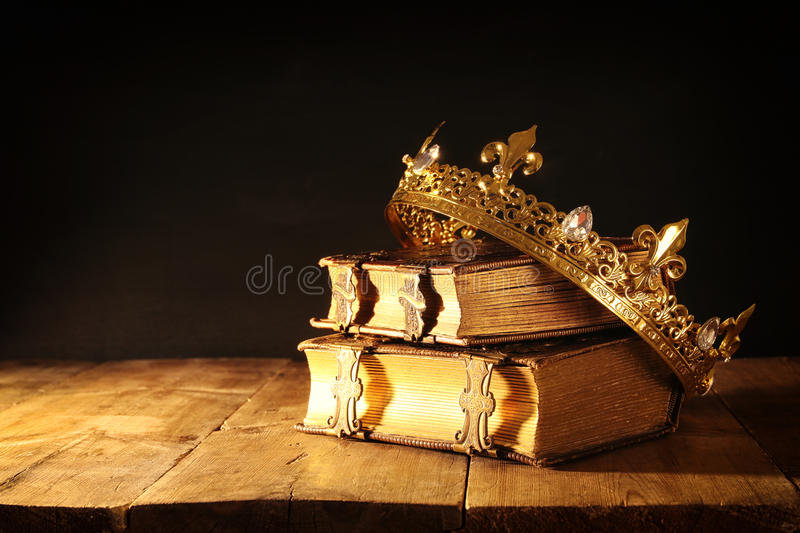Low key of beautiful queen/king crown on old books. vintage filtered. fantasy medieval period. Low key image of beautiful queen/king crown on old books. vintage stock images
