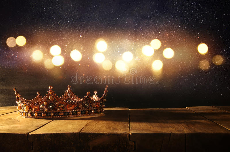 Low key of beautiful queen/king crown over wooden table. vintage filtered. fantasy medieval period. Low key image of beautiful queen/king crown over wooden table royalty free stock images