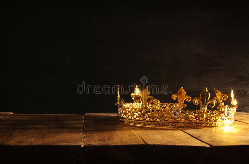 Low key of beautiful queen/king crown over wooden table. vintage filtered. fantasy medieval period. Low key image of beautiful queen/king crown over wooden table royalty free stock photography