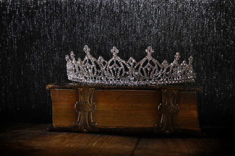 low key of diamond queen crown on old book stock photos