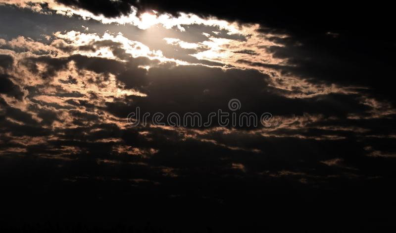 LOW KEY EFFECT ON SUN BREAKING THROUGH CLOUDS royalty free stock photo