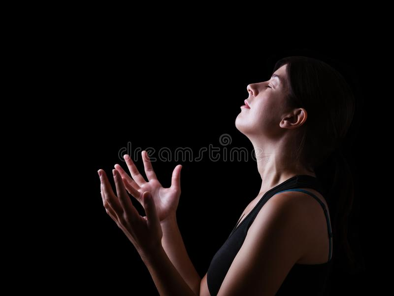 Low key of a faithful woman praying and feeling the presence or being touched by god royalty free stock images