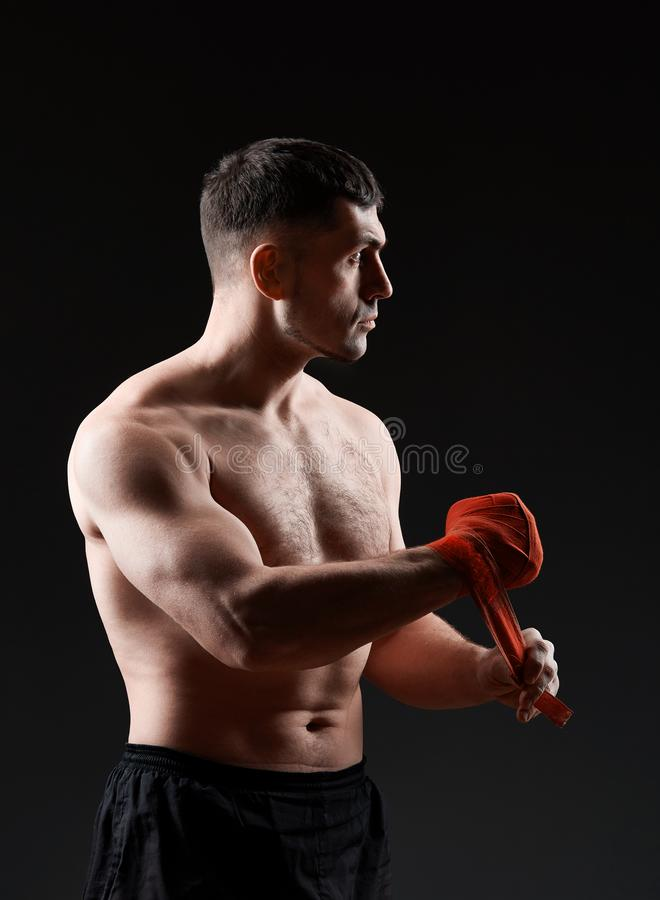 Low key studio portrait of handsome muscular fighter practicing boxing on dark blurred background royalty free stock photos