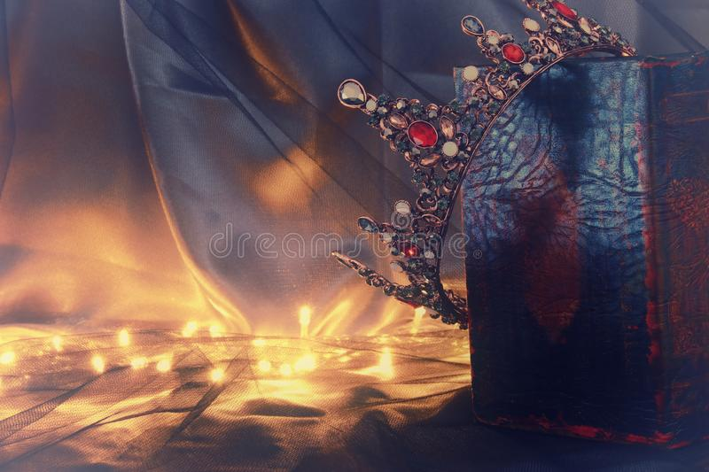 Low key image of beautiful queen/king crown on old book. fantasy medieval period. Low key image of beautiful queen/king crown on old book. fantasy medieval royalty free stock images