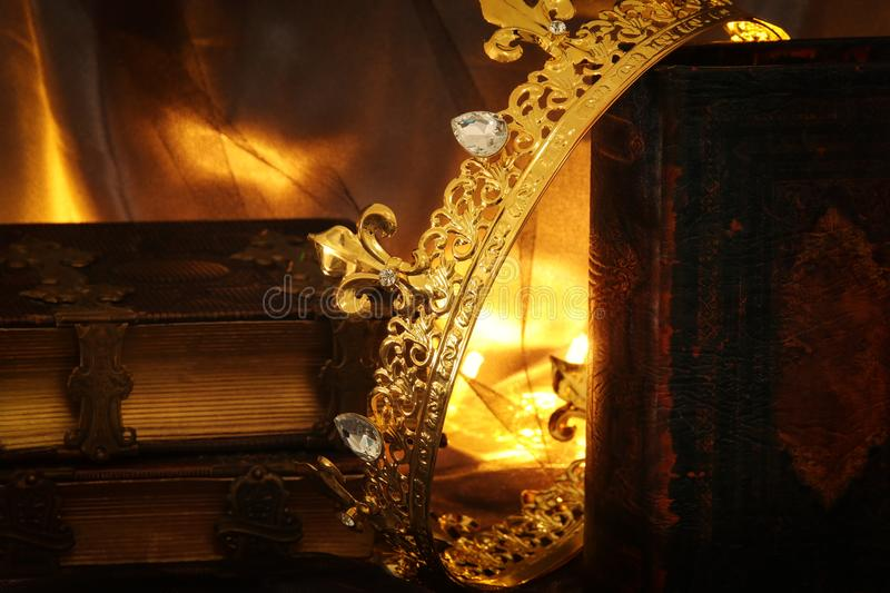 Low key image of beautiful queen/king crown on old book. fantasy medieval period. Low key image of beautiful queen/king crown on old book. fantasy medieval stock images