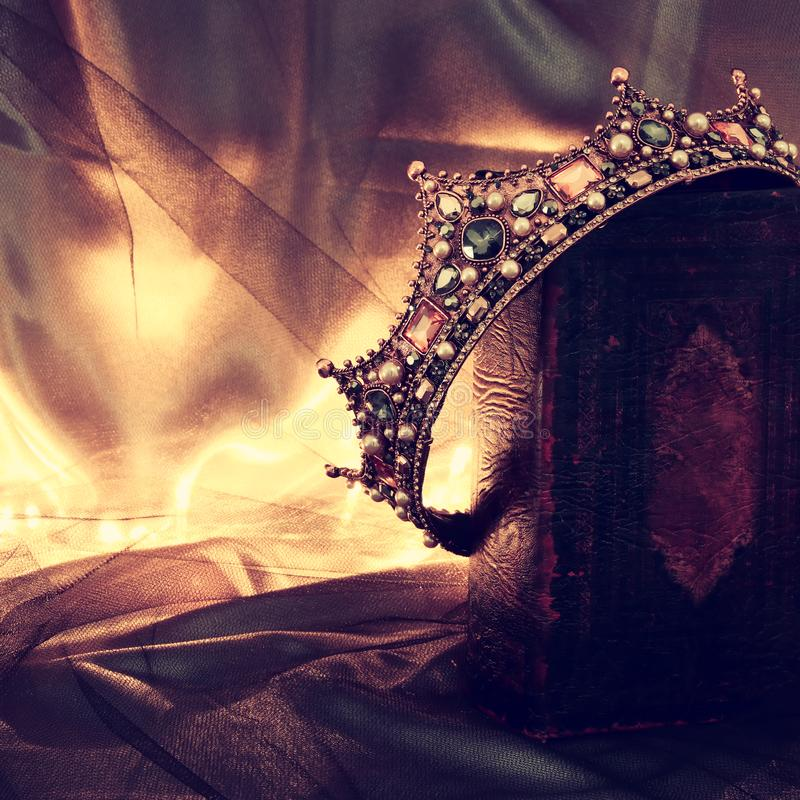 Low key image of beautiful queen/king crown on old book. fantasy medieval period. Low key image of beautiful queen/king crown on old book. fantasy medieval stock image