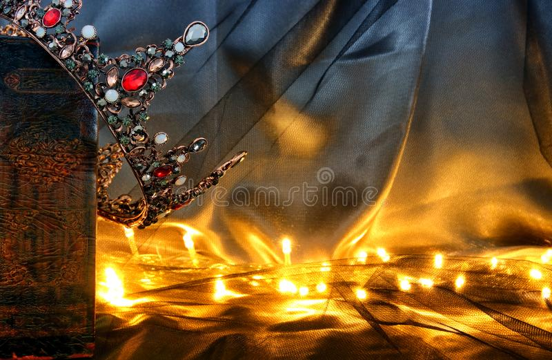 Low key image of beautiful queen/king crown on old book. fantasy medieval period. Low key image of beautiful queen/king crown on old book. fantasy medieval royalty free stock photo