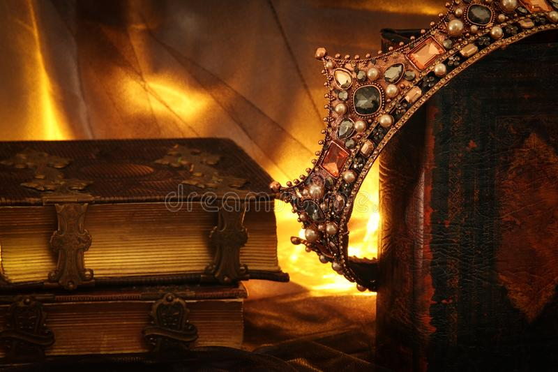 Low key image of beautiful queen/king crown on old book. fantasy medieval period. Low key image of beautiful queen/king crown on old book. fantasy medieval stock photo
