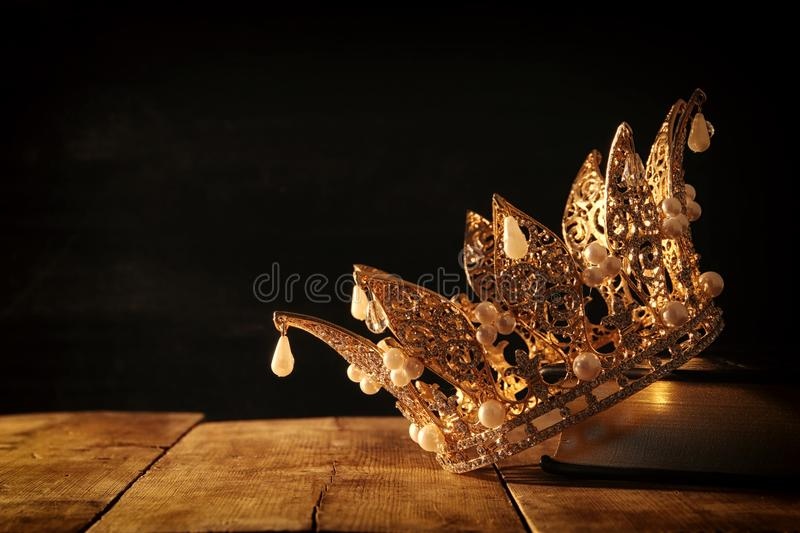 Low key image of beautiful queen/king crown on old book. fantasy medieval period. Selective focus. Low key image of beautiful queen/king crown on old book stock photos