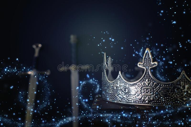 Low key image of beautiful queen/king crown over antique book next to sword. fantasy medieval period. Selective focus. Glitter. Sparkle lights royalty free stock image