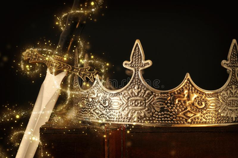 Low key image of beautiful queen/king crown over antique box next to sword. fantasy medieval period. Selective focus. Glitter. Sparkle lights royalty free stock photo