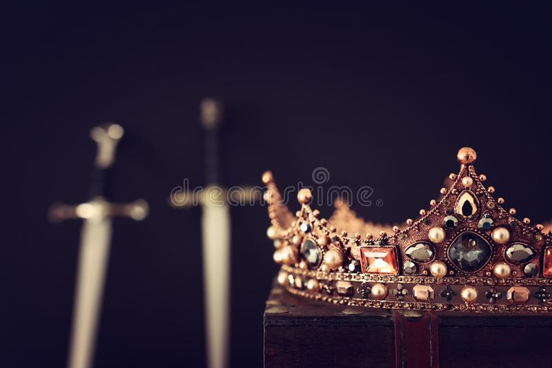 Low key image of beautiful queen/king crown over antique box and sword. fantasy medieval period. Selective focus royalty free stock photo