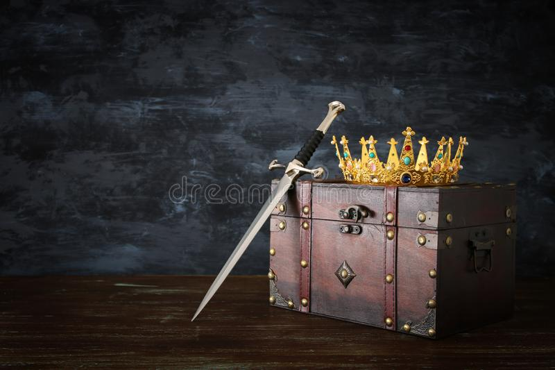 Low key image of beautiful queen/king crown and sword. fantasy medieval period. Low key image of beautiful queen/king crown and sword. fantasy medieval period royalty free stock photography