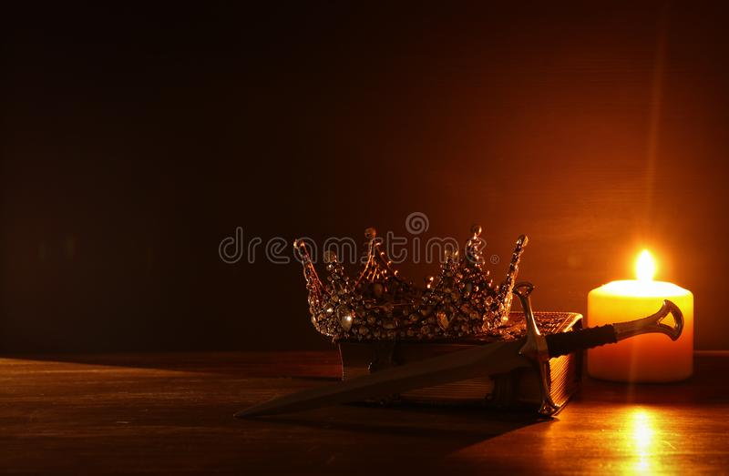 low key image of beautiful queen/king crown and sword. fantasy medieval period. Selective focus. royalty free stock images