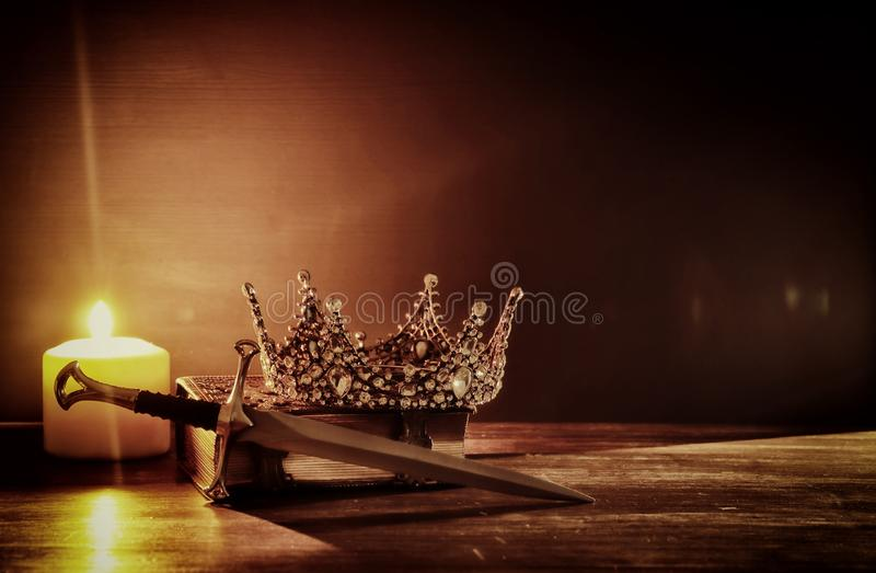 Low key image of beautiful queen/king crown and sword. fantasy medieval period. Selective focus. Low key image of beautiful queen/king crown and sword. fantasy stock photography