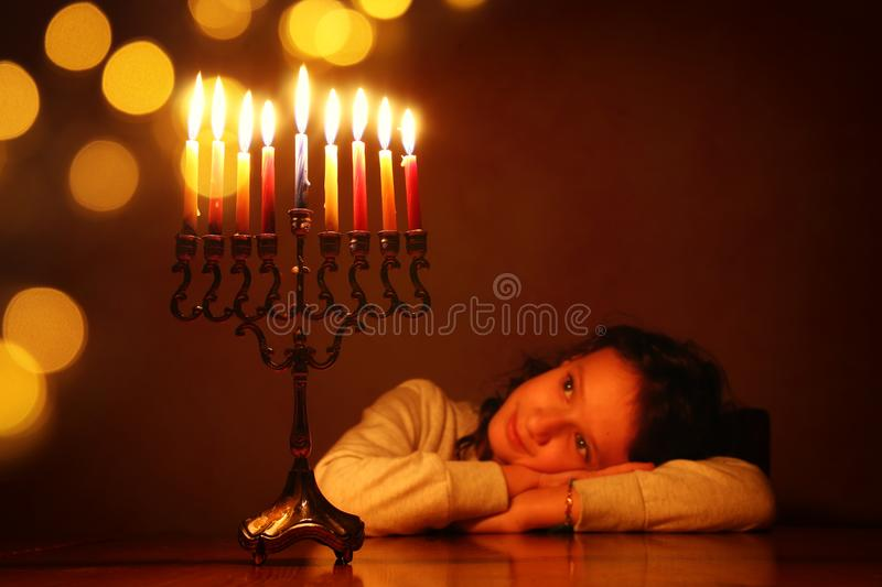 Low key image of jewish holiday Hanukkah background with cute girl looking at menorah & x28;traditional candelabra& x29; stock photos