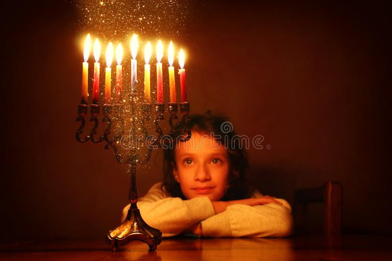 Low key image of jewish holiday Hanukkah background with cute girl looking at menorah & x28;traditional candelabra& x29; royalty free stock image