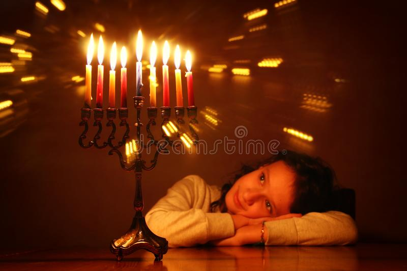 Low key image of jewish holiday Hanukkah background with cute girl looking at menorah & x28;traditional candelabra& x29; stock image