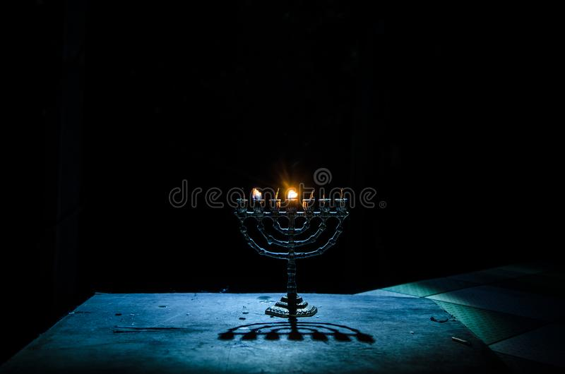 Low key image of jewish holiday Hanukkah background with menorah on dark toned foggy background stock image