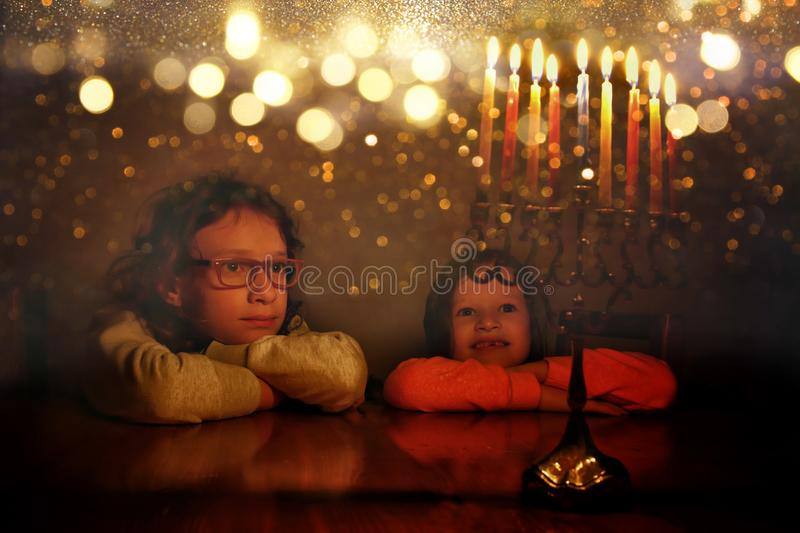 Low key image of jewish holiday Hanukkah background with two cute kids looking at menorah royalty free stock photo