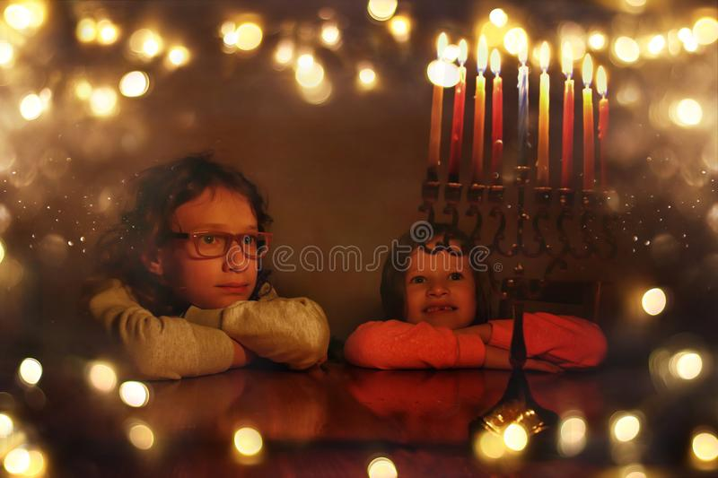 Low key image of jewish holiday Hanukkah background with two cute kids looking at menorah traditional candelabra and burning can stock image