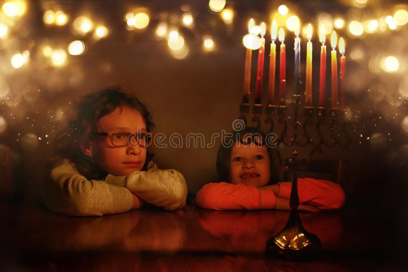 Low key image of jewish holiday Hanukkah background with two cute kids looking at menorah & x28;traditional candelabra& x29; royalty free stock image