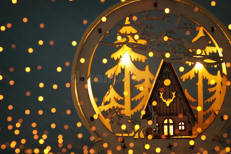 Low key Image of magical christmas scene of wooden pine forest, hut and santa claus over sleigh with deers. stock illustration