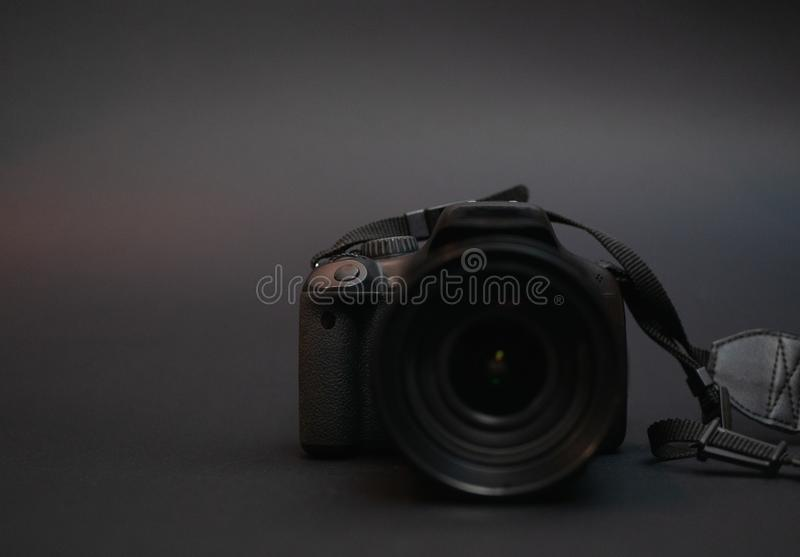 Low key image of photo camera. On dark black background. selective focus on camera body, lens blurred stock photography