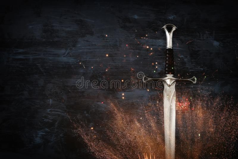 Low key image of silver sword with fire sparks. fantasy medieval period. Low key image of silver sword with fire sparks. fantasy medieval period royalty free stock image
