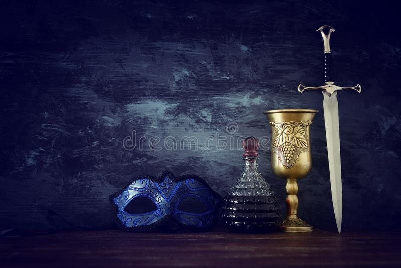 Low key image of wine cup, mysterious mask and sword. fantasy medieval period. Low key image of wine cup, mysterious mask and sword. fantasy medieval period royalty free stock image