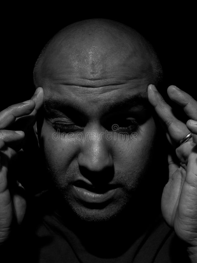 Low key photo of a bald headed man placing both hands on forehead due to a headache royalty free stock photography