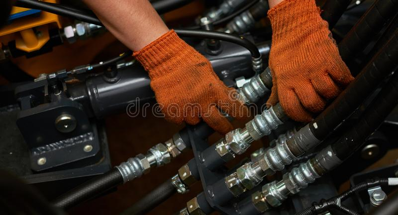 Low key photo of hydraulic pipes maintenance on heavy industry machine stock photo